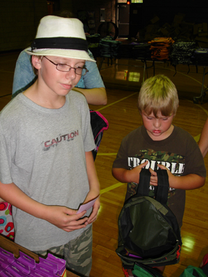 Cooper Boss, 14, in his signature hat, helps a young student make his next selection.