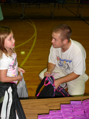 Jack Lynch, 20, gets at eye level to help a young girl fill her backpack.