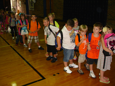 Armed with new backpacks, schoolchildren line up to return to class.