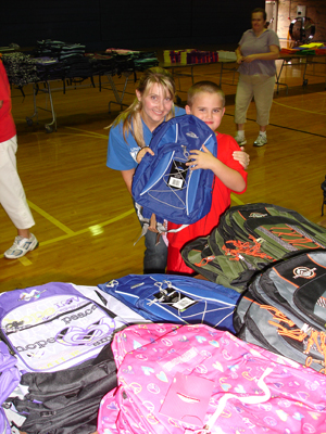 Letcher County student with Kristi Boss shows off his new backpack.