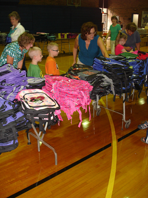 Laurie Evans helps students chose a backpack.