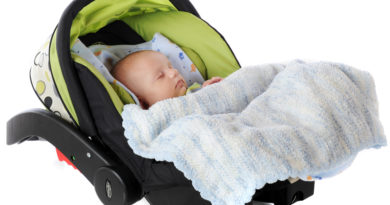 A sleeping baby in an infant car seat/carrier.  Isolated on white.