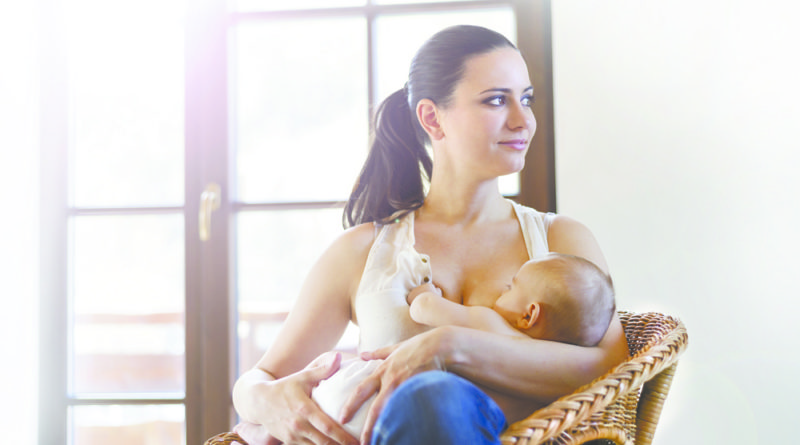 Mother breastfeeding her little baby girl in her arms.