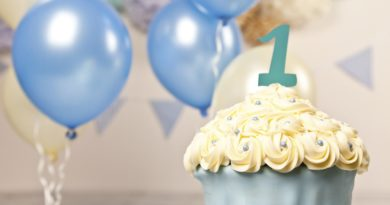 Giant beautifully decorated blue and cream cup cake surrounded by bunting and balloons.