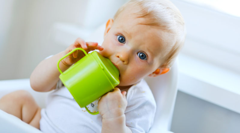 Lovely baby  sitting in chair and drinking from baby cup.