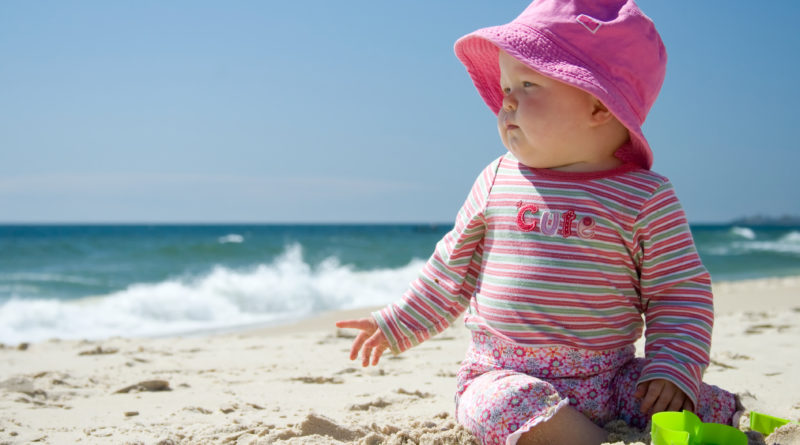 A baby girl is sun-smart while playing on a beach.