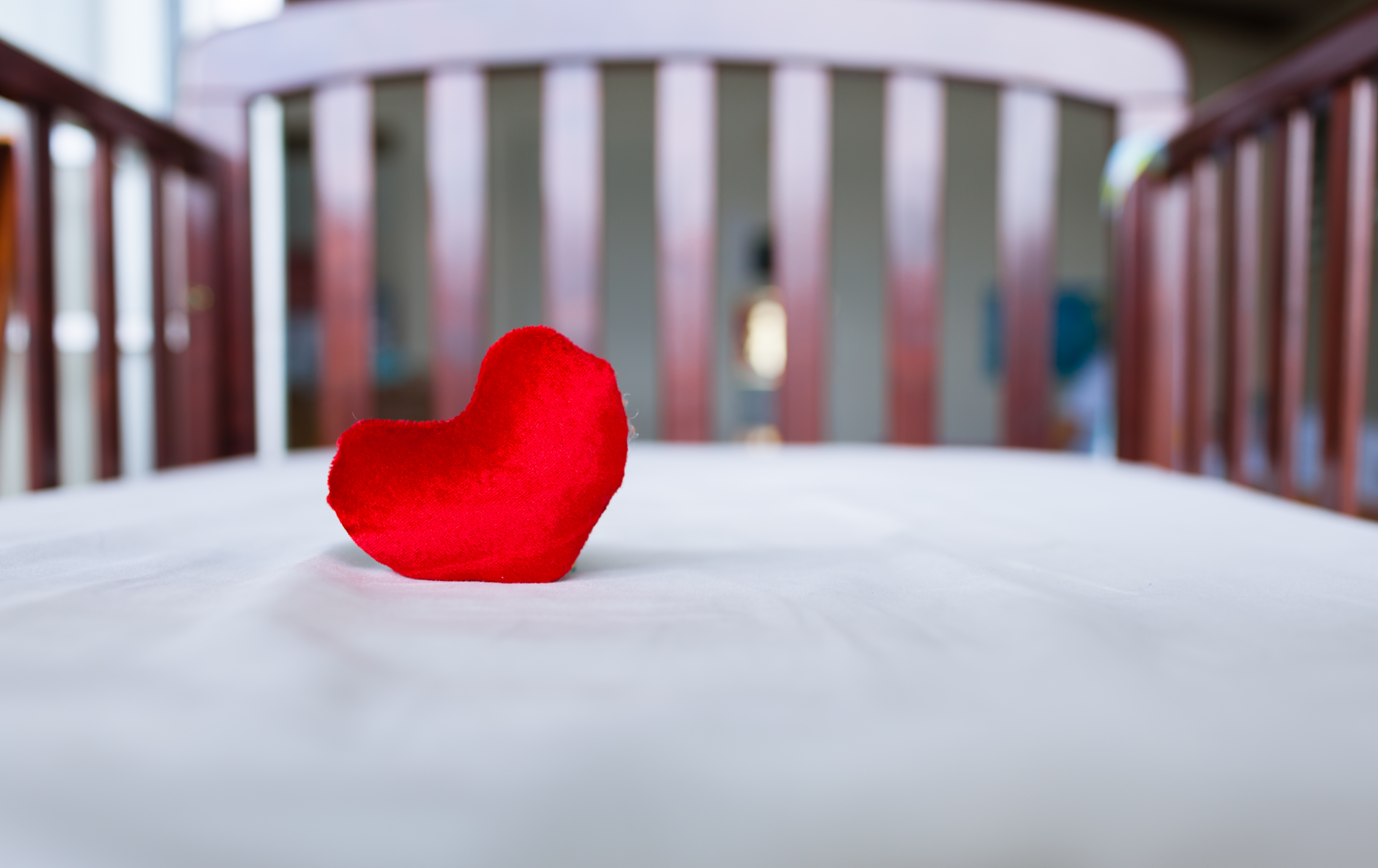 Heart in baby's crib. (child care concept)